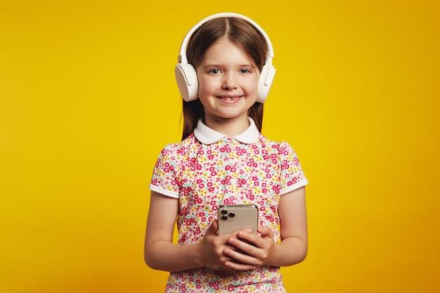 Маленькая девочка на смартфоне слушает любимую музыку в белых наушниках
