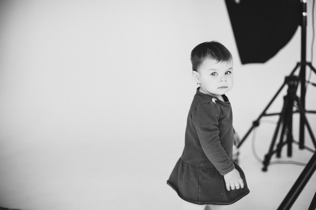 Little kid girl wearing dress looking back posing in photo studio with photography equipment. copyspace, black and white. high quality photo