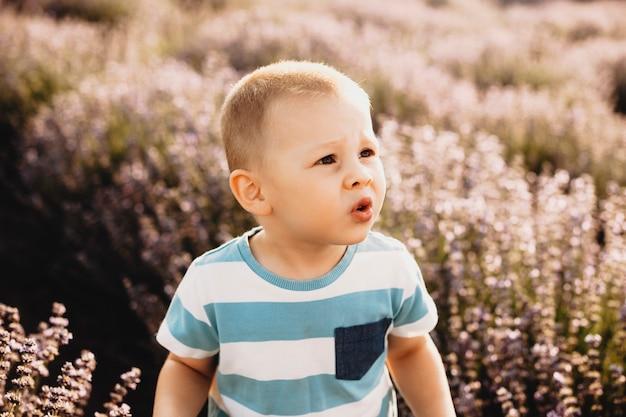 Маленький ребенок гримасничает на открытом воздухе в поле цветов.