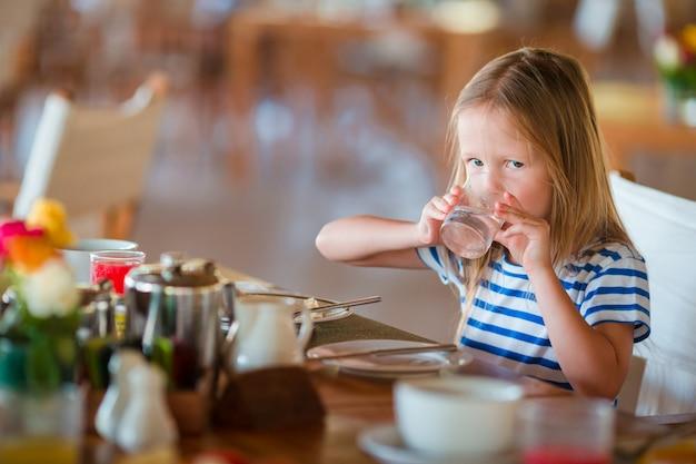 Little kid having breakfast at outdoor cafe. adorable girl drinking fresh watermelon juice enjoying breakfast.
