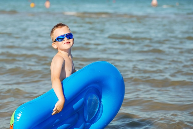 Маленький ребенок держит надувной матрас на пляже в жаркий летний день.