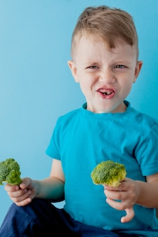 Little kid holding broccoli in his hands on blue background. vegan and healthy concept
