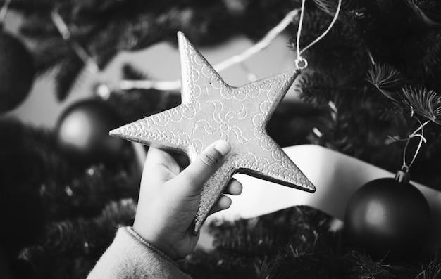 Ragazzino che tiene un ornamento stella albero di natale