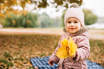 Little kid holding pack of leaves in autumn forest