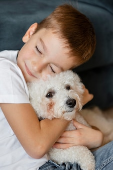 Little kid hugging his dog