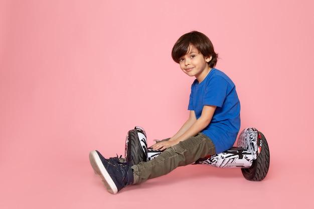 Маленький ребенок в синей футболке катается на сегвее на розовом