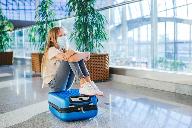 Маленький ребенок в медицинской маске в аэропорту в ожидании посадки