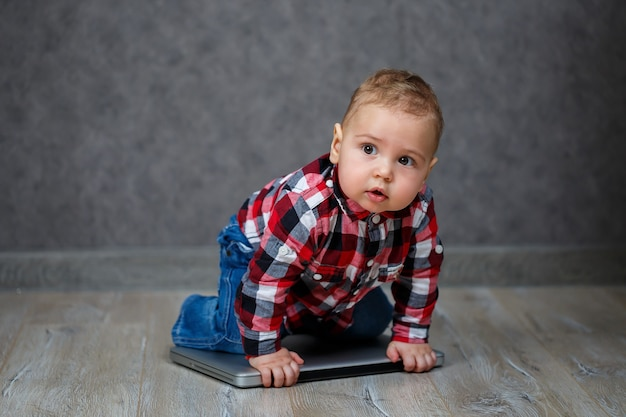 シャツを着た小さな子供がラップトップで遊ぶ
