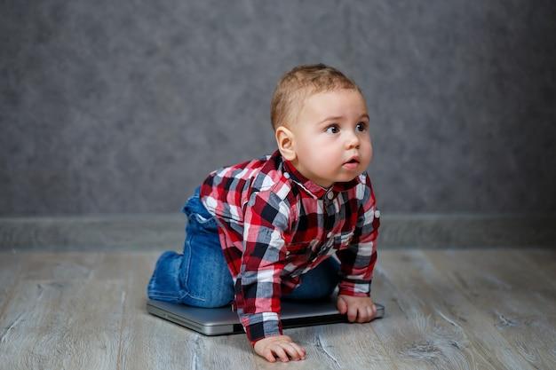 Маленький ребенок в рубашке играет с ноутбуком