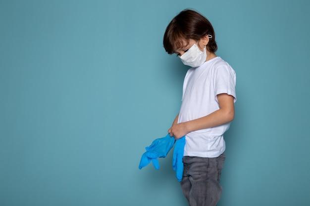 青のコロナウイルスに対する保護策としての白い保護滅菌マスクと青い手袋の小さな子供