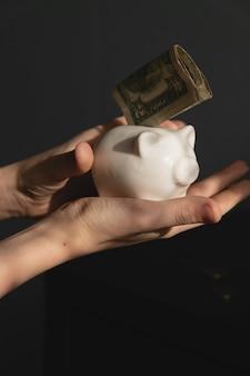 작은 꼬마 투자자가 첫 미국 달러를 저금통에 넣었습니다. 미래의 개념에 대 한 돈을 절약하는 아이.