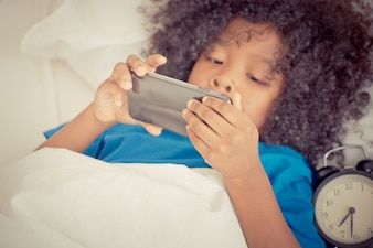 Little kid is playing with mobile phone on bed with alarm clock