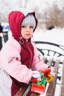 小さな子供は公園で冬におもちゃで遊んでいます
