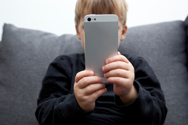 Little kid is sitting alone on sofa and looking in his phone