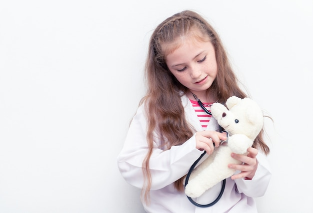 Little kid is using doctor suit and equipment to check teddy bear health