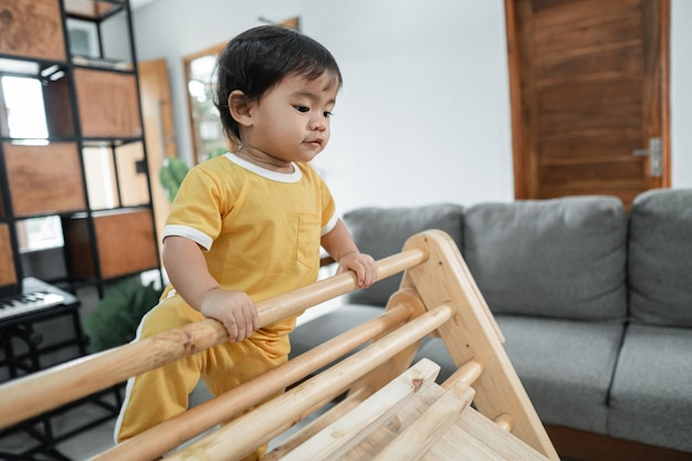 Little kid looks down while climbing on the pikler triangle toy in the living room