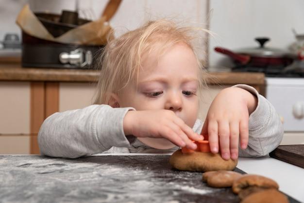 Маленький ребенок делает печенье. готовим печенье с детьми. обучение детей.