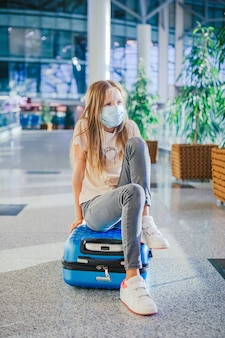 Little kid in medical mask in airport waiting for boarding