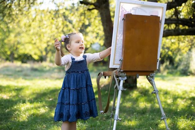 Маленький ребенок, рисующий на открытом воздухе в парке. детское творчество. милая девушка в джинсовом платье, улыбается и рисует красочными красками в летнем саду. талантливый ребенок-живописец.