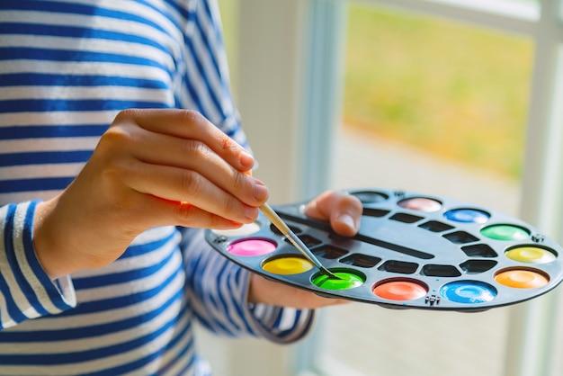 Маленький ребенок, рисующий акварельной краской в домашней школе, крупным планом руки, окунающей кисть в красочную краску.