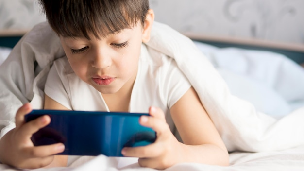 Little kid on phone with bed