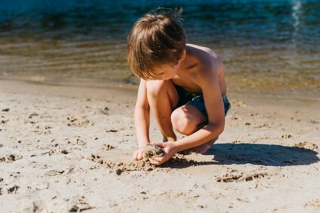 Маленький ребенок играет на пляже во время летних каникул