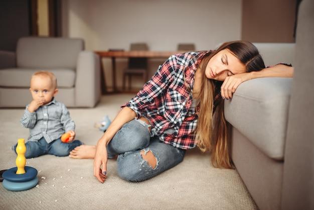 Маленький ребенок играет на полу, мама спит