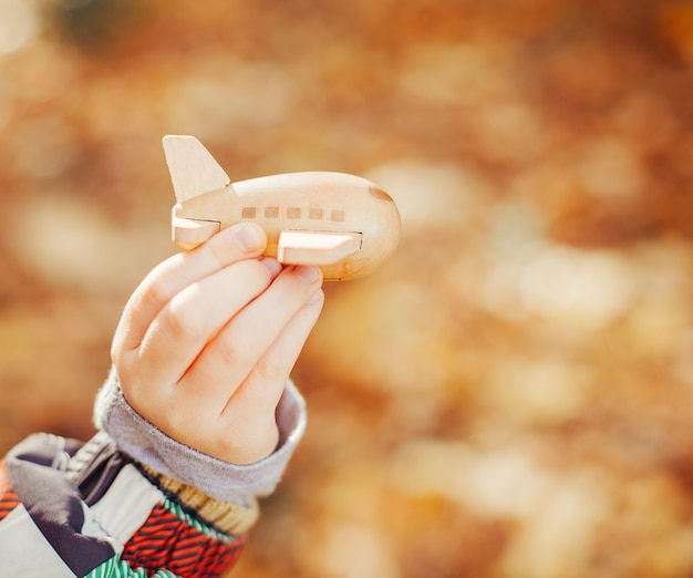 Little kid playing with wooden toy plane