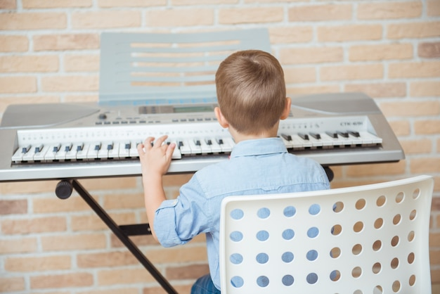 Little kid practicing electric piano during music session in academy