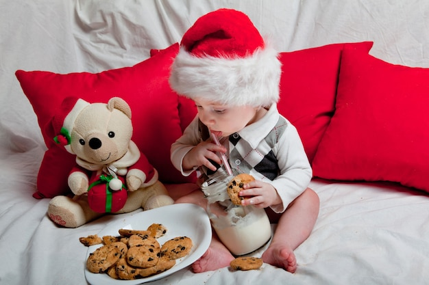 A little kid in a red cap eats a cookies and milk