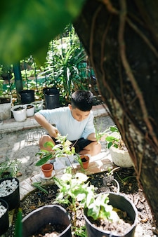 Little kid repotting plants in backyard on sunny summer day