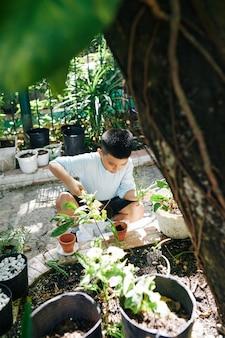 화창한 여름 날에 뒷마당에서 식물을 화분에 심는 작은 아이