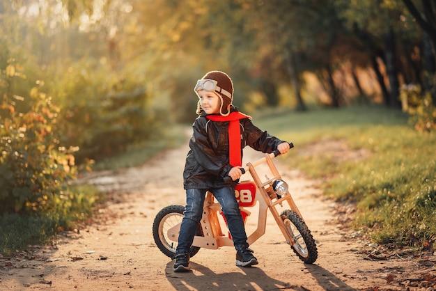가을에 겉옷에 균형 자전거를 타는 어린 아이
