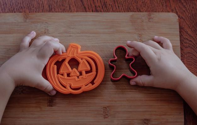 伝統的なハロウィーンのクッキーを作る小さな子供の手。木製のテーブルの背景に休日のクッキーのカッター。クッキーの準備。ビスケットを作る手順。上面図。