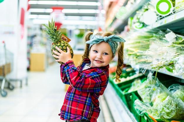 슈퍼마켓에서 파인애플과 함께 서있는 작은 아이