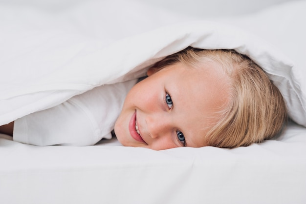 Little kid staying in bed while looking at the camera close-up