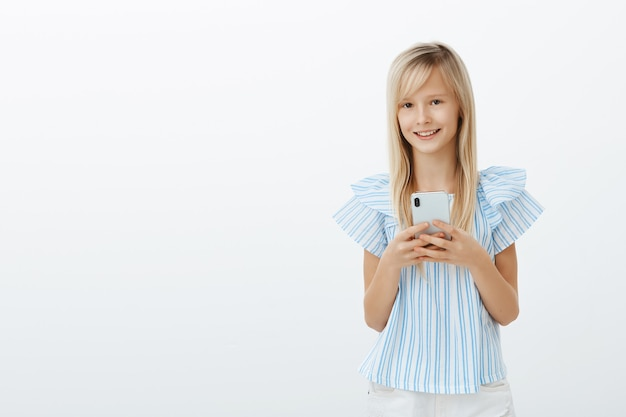 Little kid stole dads cellphone to play games. portrait of charming happy young girl with blond hair, holding smartphone and smiling broadly, watching cartoons or messaging with friends over gray wall