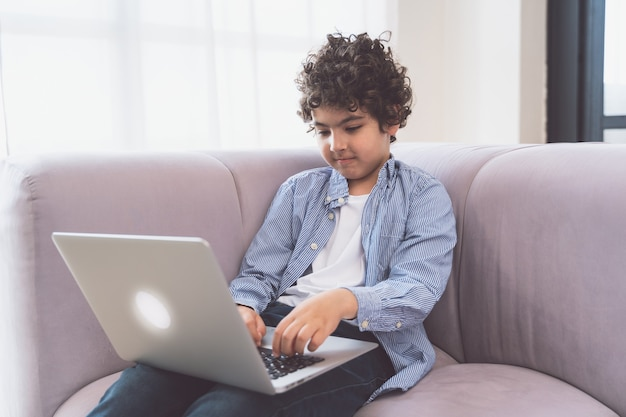 그의 노트북에서 공부 하는 작은 아이. 어린 시절과 기술에 대한 개념