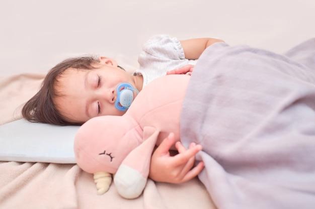 Маленький ребенок спит в постели, обнимая мягкую плюшевую пушистую игрушку, просыпается с пустышкой во рту