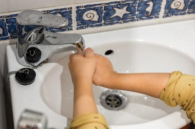 어린 아이는 집 화장실에 있는 작은 세면대의 수도꼭지 아래 흐르는 물로 손을 씻습니다. 아이들은 깨끗하고 개인 위생 개념입니다. 바이러스로부터 사람들을 보호
