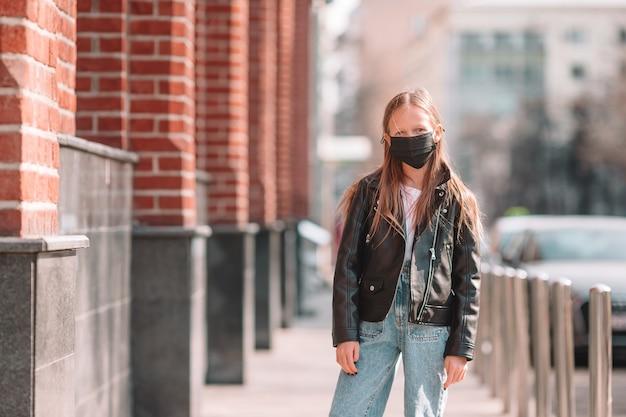 屋外でウイルスを防ぐためのマスクを身に着けている小さな子供。コロナウイルスに対する保護