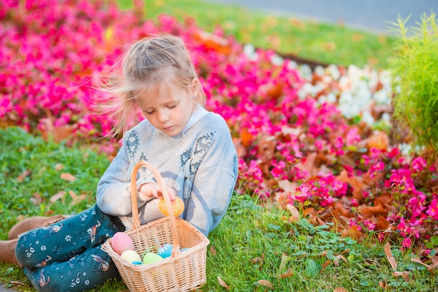 Little kid wearing bunny ears with a basket full of easter eggs on spring day outdoors