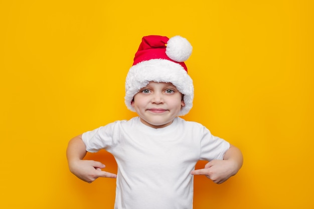 A little kid in a white tshirt and a red santa hat points with his fingers on it showing copy space