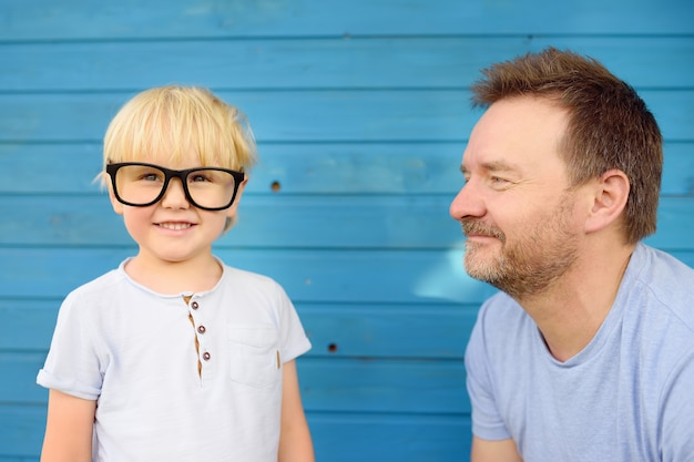 Little kid with big glasses and his father on blue wooden backgraund. clever childs