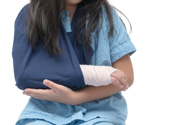 Little kid with broken hand isolated on white background, kid after accident