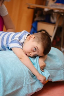 Little kid with cerebral palsy has musculoskeletal therapy by doing exercises in body fixing
