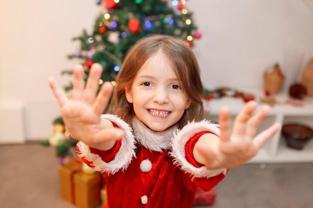 Маленький ребенок с руками, полными рождественский блеск