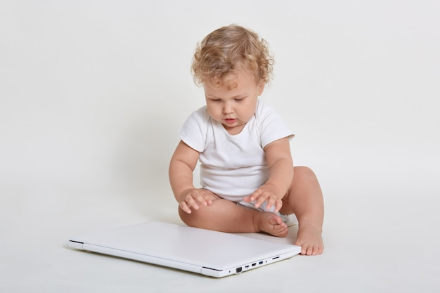 Little kid with laptop sitting on ground, closed laptop computer with great interest