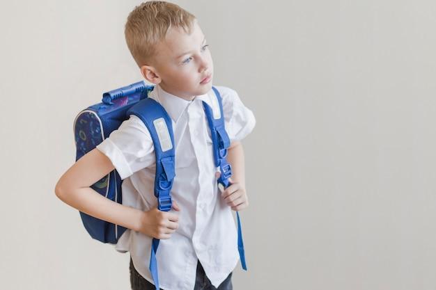 Little kid with rucksack in studio