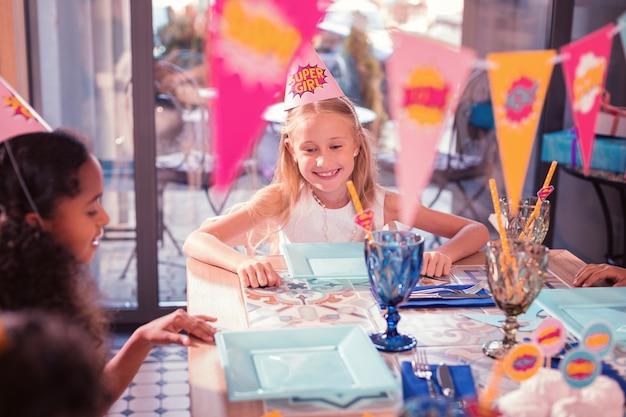誕生日パーティーに出席し、テーブルに座っている小さな子供たち